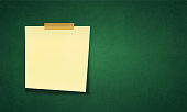 A horizontal vector illustration of a sticky note over a green board. Stuck with a brown color adhesive tape on top, Left lose from bottom. The adhesive note is yellow and is placed or positioned towards the left. Slightly angled. Copy space. No people, no text. The bottom right corner is a bit curled up and has shadow, shadows. The ends of the tape do not have a neat cut and are torn, ripped by hand.