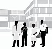 A vector silhouette illustration of a medical care crew standing outside of a hospital including a doctore, nurse, medical office assiatant, and paramedic.