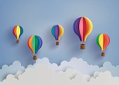 Origami made colorful hot air balloon and cloud.paper art style.