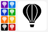 Hot Air Balloon Icon Square Button Set. The icon is in black on a white square with rounded corners. The are eight alternative button options on the left in purple, blue, navy, green, orange, yellow, black and red colors. The icon is in white against these vibrant backgrounds. The illustration is flat and will work well both online and in print.
