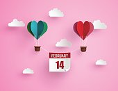Illustration of love and valentine day,Origami made hot air balloon in a heart shape with massege 14 february floating on the sky.paper art and craft style.