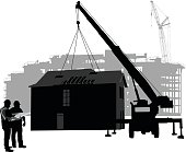 A vector silhouette illustration of a prefabricated building being placed by  a crane with a safty barrier around it.  A partitially constructed building is in the background.  Two construction workers look over blue prints.