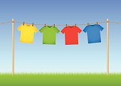 Hung T-shirts on washing line with grass and blue sky in the background