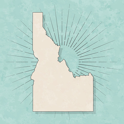 Map of Idaho in a trendy vintage style. Beautiful retro illustration with old textured paper and light rays in the background (colors used: blue, green, beige and black for the outline). Vector Illustration (EPS10, well layered and grouped). Easy to edit, manipulate, resize or colorize.