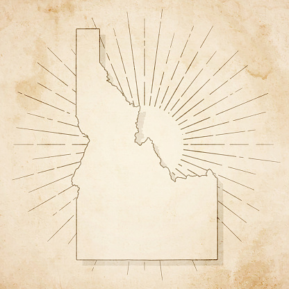 Map of Idaho in a trendy vintage style. Beautiful retro illustration of an antique map with light rays in the background and on old textured paper. Included: Realistic texture of an old parchment (colors used: sepia, beige, brown). Vector illustration (EPS10, well superimposed and grouped). Easy to edit, manipulate, resize or colorize.