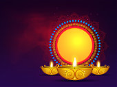 Illuminated golden oil lamps with vintage circular frame given for your message on purple background for Diwali Festival. Can be used as greeting card design.