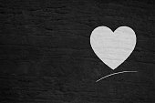 Horizontal vector illustration of one white colored textured heart over a black wooden textured  background. A curved line under the heart and blank space all around the heart, which is towards the right in the illustration. The texture of the heart is like it is drawn with a white chalk over a blackboard. Apt for love Greeting card, postal, background, notes or invitation with copy space for text. No text. No people. Valentine's Day greetings or wishes.