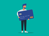 istock Illustration of young man holding giant credit card 1218285052