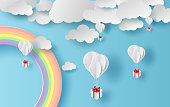 illustration summer season landscape with a rainbow on blue sky background. Balloons gift floating on air with paper art. Creative design Paper cut and craft style. pastel colorful tone simple. vector.