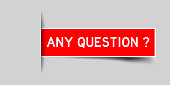 Inserted red color label sticker with word any question on gray background