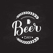International Beer day calligraphy hand lettering on chalkboard background. Vector template for banner, typography poster, flyer, sign, postcard, logo design, etc.