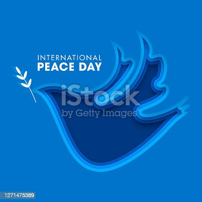 International Peace Day Text on Blue Paper Layer Cut Dove Bird Shape Background.