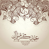 Islamic calligraphy of text Eid Mubarak on floral decorated background.