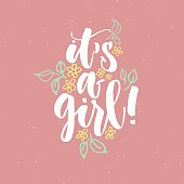 It's a girl Hand written calligraphy poster. Brush lettering white color on cute pink girl background with flowers and leaves. Poster or greeting card, invitation on baby shower.