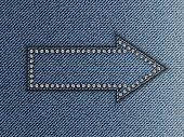 Blue jeans arrow with diamonds on jeans background.