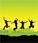 Silhouettes of people jumping against a beautiful fresh green landscape.