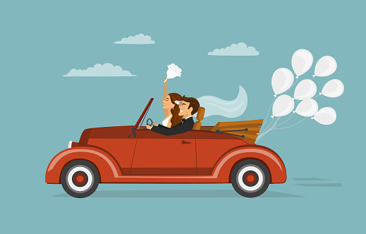 just married couple, newlywed, bride and groom on a roadtrip in vintage retro car with balloons after wedding ceremony
