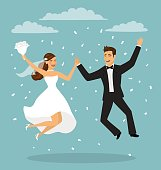 Just married funny couple, bride and groom jumping after wedding ceremony