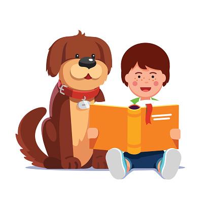 Kid boy reading book sitting next his dog friend