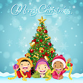 Multi-ethnic group of children lying down in front of the Christmas tree to celebrate Christmas time.