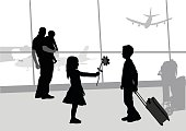 A vector silhouette illustration of a young girl give a young boy a flowerat an airport terminal.  A father holds his young son in the background.
