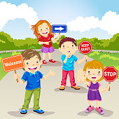 Four kids holding various placards including welcome, stop, keep quite and directional arrow.