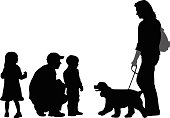 A vector silhouette illustration of children carefully approaching a woman's dog.  The father is crouched down with the kids encouraging them.