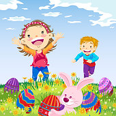 Boy and girl playing Easter egg hunt on nature.