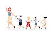 istock Kindergarten children walking behind teacher with safety rope. 1216918121