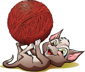 Cute image of a kitten playing with a ball of yarn.