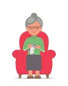 Knitting. Grandma sitting in a cozy armchair knitting.
