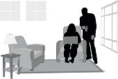 Silhouette vector illustration of a couple in their living room looking at something on her laptop
