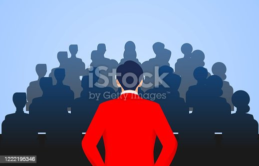 1069233370 istock photo Leader stands in front of a group of people speaking 1222195346