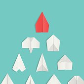 Leadership concept with red paper airplane leading among white.