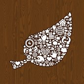 Ecological concept with human heart symbol consisting of recycle icons, on dark wooden background.