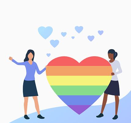 Lesbian couple holding rainbow heart
