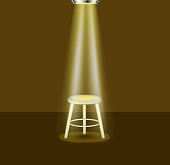 Light shines on empty stool on stage on brown background