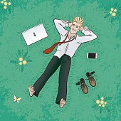 Young successful businessman, lying down and relaxing on grassplot with a dandelion flowers; beside an electronic gadgets: laptop and smartphone.