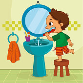 Little boy brushing his teeth in the bathroom.