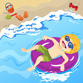 A little boy wearing sunglasses and sunbathing in an inflatable ring, the inner ring floating on the seaside, the sand shovel, bucket and flip-flop is on the sand with a crab along the beach