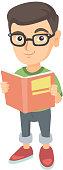 Little caucasian schoolboy reading a book