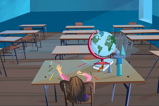 Little girl in an empty classroom waiting for a class to begin