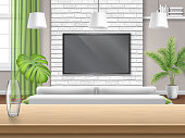 View on living room with sofa and tv through the wooden bar table. Bright interior with a brick wall and a window with a green curtain.