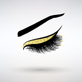 long lashes with gold decor on a light background