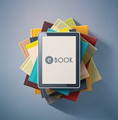 Looking down on E book on top of pile of books