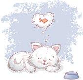 Cute kitten dreaming of fish.