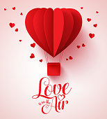 Love is in the air typography for valentines day with paper cut red heart shape balloon flying and hearts decorations in white background. Vector illustration.