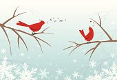 Retro stylized red birds perched on snow covered bare branches in a forest in winter with snowflakes drifting softly around.  One bird sings sweetly to the other bird, who reacts with love feelings.