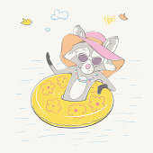 Lovely cute raccoon girl sitting on the yellow inflatable circle. Young swimmer in the sunglasses, the Hawaiian wreath and the summer hat.