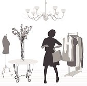 A vector silhouette illustration of a woman trying on clothes at an elegant clothing store.